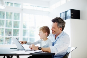 Man sitting at desk with son on his knee with laptop computer and paperwork - B2B