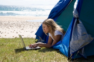Young woman in tent using laptop at beach, side view